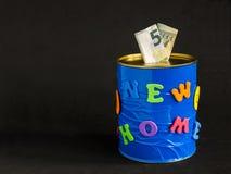 Tirelire faite main avec la nouvelle inscription à la maison et deux euro billets de banque Fond noir Photo stock