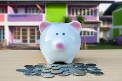 Tirelire mignonne sur une pile d'argent comptant Concept de l'épargne et d'argent Photographie stock libre de droits