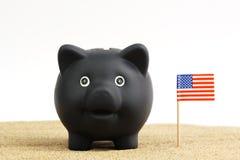 Tirelire noire se tenant à côté du drapeau des Etats-Unis sur le sable avant le fond blanc Photographie stock libre de droits