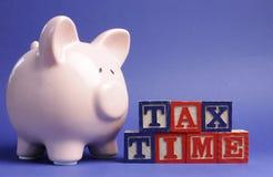 Tirelire rose avec des lettres de module de temps d'impôts Photo libre de droits