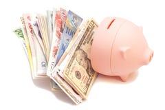Tirelire rose avec les billets de banque internationaux Photo stock