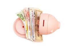 Tirelire rose avec les billets de banque internationaux Photo libre de droits