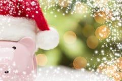 Tirelire rose avec Santa Hat sur des flocons de neige Image libre de droits