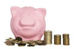 Tirelire rose et une pile des pièces de monnaie devant elle sur un fond blanc photos stock