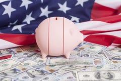 Tirelire rose sur des dollars avec le drapeau américain Image stock