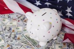 Tirelire sur des dollars avec le drapeau américain Photographie stock libre de droits