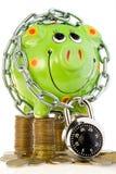 Tirelire verrouillée sur des pièces de monnaie Images stock