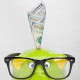 Tirelire verte au-dessus de diagramme de marché boursier avec 100 dollars de billet de banque - rapport 1 à 1 Image libre de droits