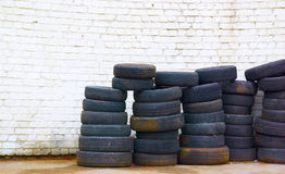 Tires. Old worn tires at the white brick-wall Stock Images