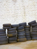 Tires. Old worn tires at the white brick-wall Royalty Free Stock Photo