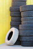 Tires against yellow wall. Tires stacked up against a yellow wall Stock Photography