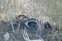 Tires Dumped in a Field illegally. Used and discarded rubber tires dumped illegally in an open field Royalty Free Stock Image