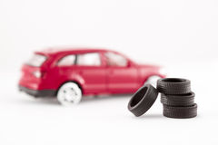 Tires in front of toy car. Four tires (from a toy car) piled up and focused - the defocused toy car (without tires) serves as a background royalty free stock photos