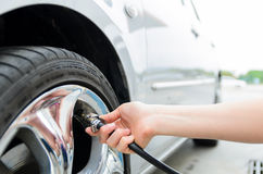 Tires pressure. Detail of hand pumping air to tire for increasing pressure Stock Photos