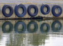 Tires protecting the boats in the harbor Stock Photos