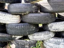 Tires stacked on top of each other. Large pile of tires dump. Illegal garbage dump. The concept of ecology pollution stock photos