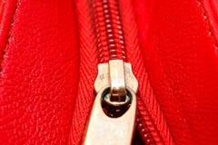 Tirette en métal sur la fin rouge intense de détail de veste en cuir ou de bourse vers le haut du macro E photographie stock libre de droits