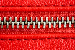 Tirette en métal sur la fin rouge intense de détail de veste en cuir ou de bourse vers le haut du macro La tirette est étroitemen image stock