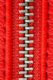 Tirette en métal sur la fin rouge intense de détail de veste en cuir ou de bourse vers le haut du macro La tirette est étroitemen photo libre de droits