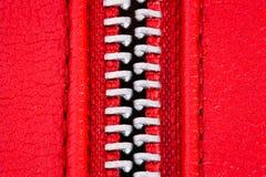 Tirette en métal sur la fin rouge intense de détail de veste en cuir ou de bourse vers le haut du macro La tirette est ouverte en photo libre de droits