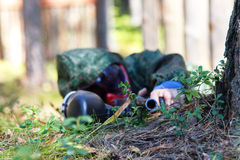 Tireur isolé avec l'arme à feu de paintball déguisée dans l'herbe Foyer sur le Ba Photographie stock