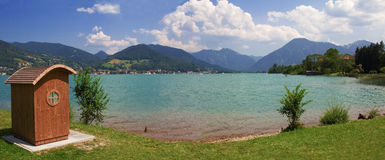 Tiri con la sedia di spiaggia di legno al tegernsee della riva del lago, Baviera Immagine Stock