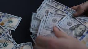Tiri dell'uomo sulle banconote in dollari della tabella 100 archivi video