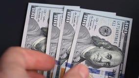Tiri dell'uomo sulle banconote in dollari della tabella 100 video d archivio
