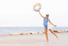 Tiri gli occhiali da sole d'uso felici e variopinti della donna ed il cappello in secco della spiaggia che ha divertimento dell'e Fotografia Stock