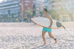 Tiri gli sport acquatici in secco che praticano il surfing l'uomo con funzionamento del surf del corpo immagine stock