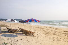 Tiri il letto in secco con l'ombrello di spiaggia, repared affinchè gli ospiti prendano il sole Immagini Stock