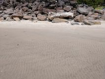 Tiri il mucchio in secco dei massi e del legname galleggiante con la sabbia della spiaggia nella priorità alta alla costa dell'Or fotografia stock libera da diritti