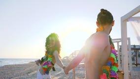 Tiri il partito in secco al movimento lento di lungomare, vacanze estive nell'amore sul litorale, corone del fiore sul collo di g stock footage