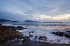 Tiri il tramonto in secco sull'isola di festa con l'alta onda Immagine Stock