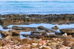 Tiri la linea in secco della costa con le pietre e l'oceano giallo sabbia ed azzurrato dei ciottoli, Fotografia Stock Libera da Diritti