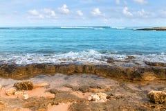 Tiri la linea in secco della costa con le pietre e l'oceano giallo sabbia ed azzurrato dei ciottoli, immagini stock