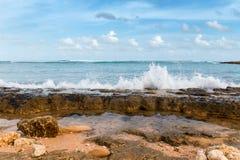 Tiri la linea in secco della costa con le pietre e l'oceano giallo sabbia ed azzurrato dei ciottoli, Fotografie Stock