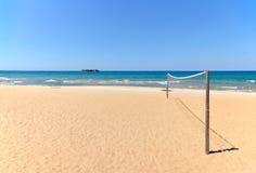 Tiri la rete in secco di pallavolo sulla spiaggia sabbiosa con il mare Fotografie Stock Libere da Diritti