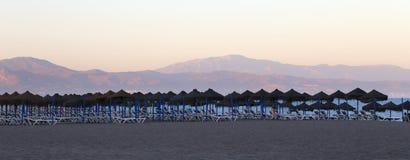 Tiri la sedia di salotto e l'ombrello in secco di spiaggia alla spiaggia sabbiosa sola Costa del Sol (costa del Sun), Malaga in A Fotografie Stock Libere da Diritti