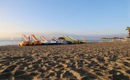 Tiri la sedia di salotto e l'ombrello in secco di spiaggia alla spiaggia sabbiosa sola Costa del Sol (costa del Sun), Malaga in A Fotografia Stock