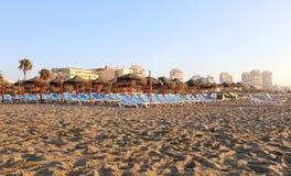 Tiri la sedia di salotto e l'ombrello in secco di spiaggia alla spiaggia sabbiosa sola Costa del Sol (costa del Sun), Malaga in A Fotografie Stock