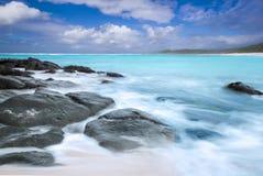 Tiri la vista in secco con le onde, le rocce e le nuvole fotografia stock libera da diritti