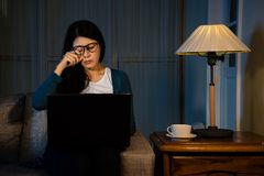Tiring lady feeling eyes uncomfortable. When using portable computer all day and working overtime at night in the office meeting room sitting on the couch Stock Photography