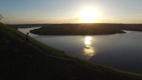 Tiro épico aéreo de un hombre que camina abajo al borde de la orilla del río como silueta en puesta del sol hermosa almacen de metraje de vídeo