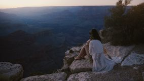 Tiro épico del fondo de la cámara lenta de la mujer joven feliz con el pelo del vuelo que se sienta en Grand Canyon increíble en  almacen de video