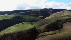 Tiro aéreo épico de las tierras y de las colinas anchas de la hierba almacen de metraje de vídeo