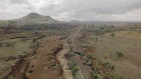 Tiro aéreo africano seco del paso elevado de la cama de río con las vías del tren en la estación seca almacen de video