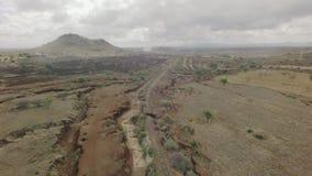 Tiro aéreo africano seco del paso elevado de la cama de río con las vías del tren en la estación seca almacen de metraje de vídeo