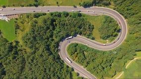 Tiro aéreo asombroso del tráfico de coche en el camino de la serpentina del bosque almacen de video