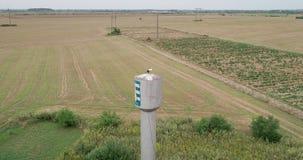 Tiro aéreo: Cegonha no ninho na torre de água na vila vídeos de arquivo